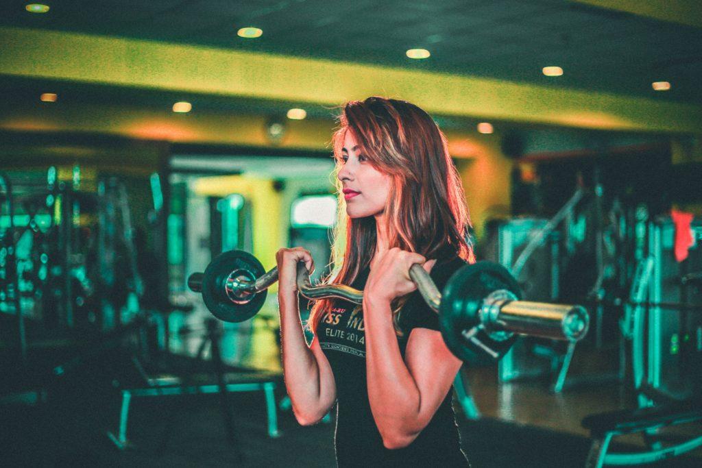Jovem mulher realizando exercício de Rosca Bíceps com barra.
